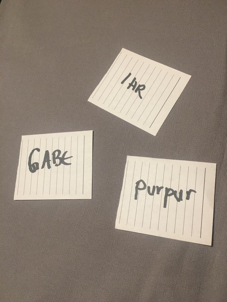 auf dunklem Grund drei weiße Notizzettel mit jeweils einem Wort als Aufschrift. Die Worte sind: pur pur, Gabe und ihr