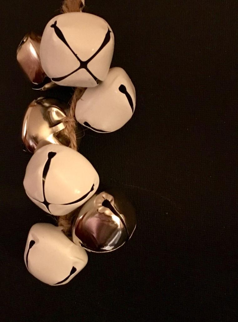 vor schwarzem Hintergrund eine Traube aus weißen und silbrig glänzenden Glockenschellen