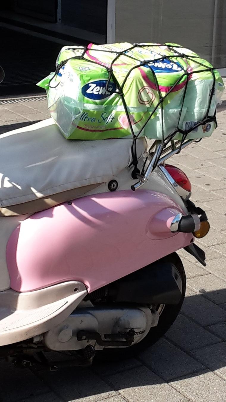 Hinterteil einer rosa Vespa; mit Klopapierrollen auf dem Gepäckträger.