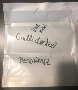 ein heller Notizzettel auf dunklen Untergrund. Darauf die Wörter: Gullideckel. USB Kabel. Resonanz.